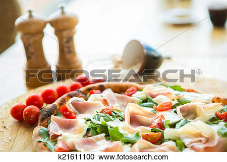 Stock Photography of Pizza with cherry tomatoes, prosciutto and.