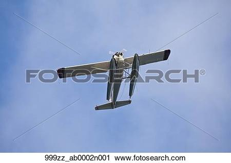 Stock Photography of Float plane flying directly over head against.