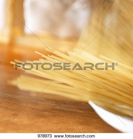 Stock Photo of Uncooked spaghetti falling into a deep plate 978973.