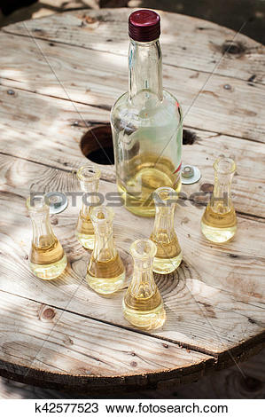 Stock Photo of Bottle of plum brandy with small glasses on wooden.