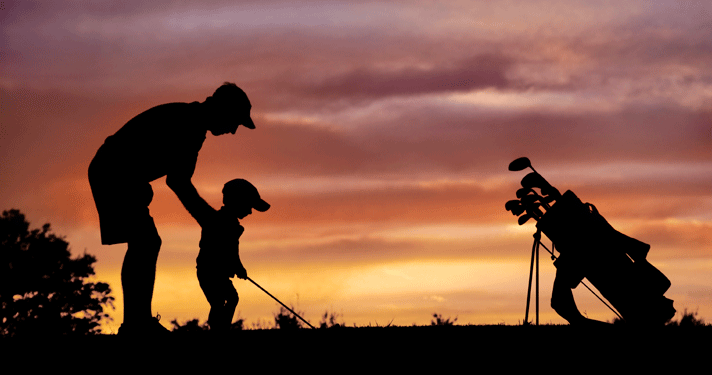Photo of Dad teaching child to golf. Beautiful silhouette.
