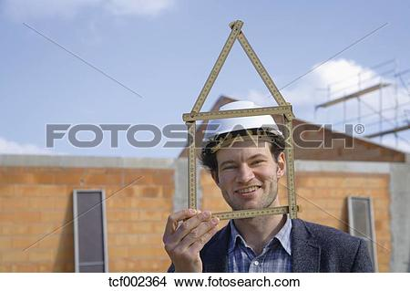 Stock Photo of Germany, Bavaria, Young man with hard hat showing.