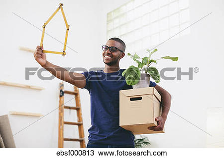 Stock Photo of Smiling young man holding cardboard box and pocket.