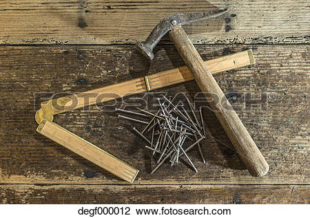 Stock Photo of Vintage hammer, nails and wooden pocket rule on.