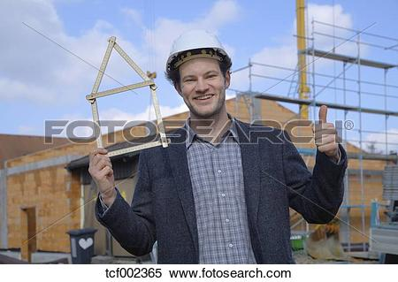 Stock Image of Germany, Bavaria, Young man with hard hat showing.