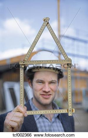 Stock Images of Germany, Bavaria, Young man with hard hat showing.