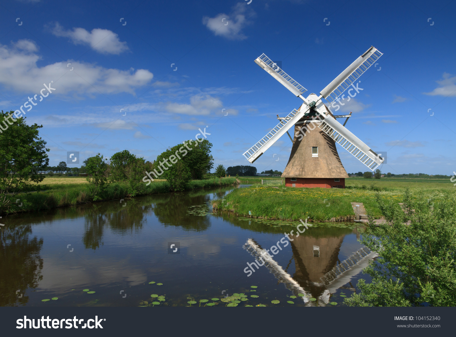 Traditional Dutch Windmill In A Polder At A Canal With Water.