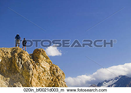 Stock Photo of Hiker standing on rock outcrop overlooking Toklat.