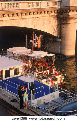 Pictures of Couple along Seine River in Paris at sunset with boats.