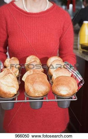 Stock Photography of Woman holding freshly baked popovers on a.