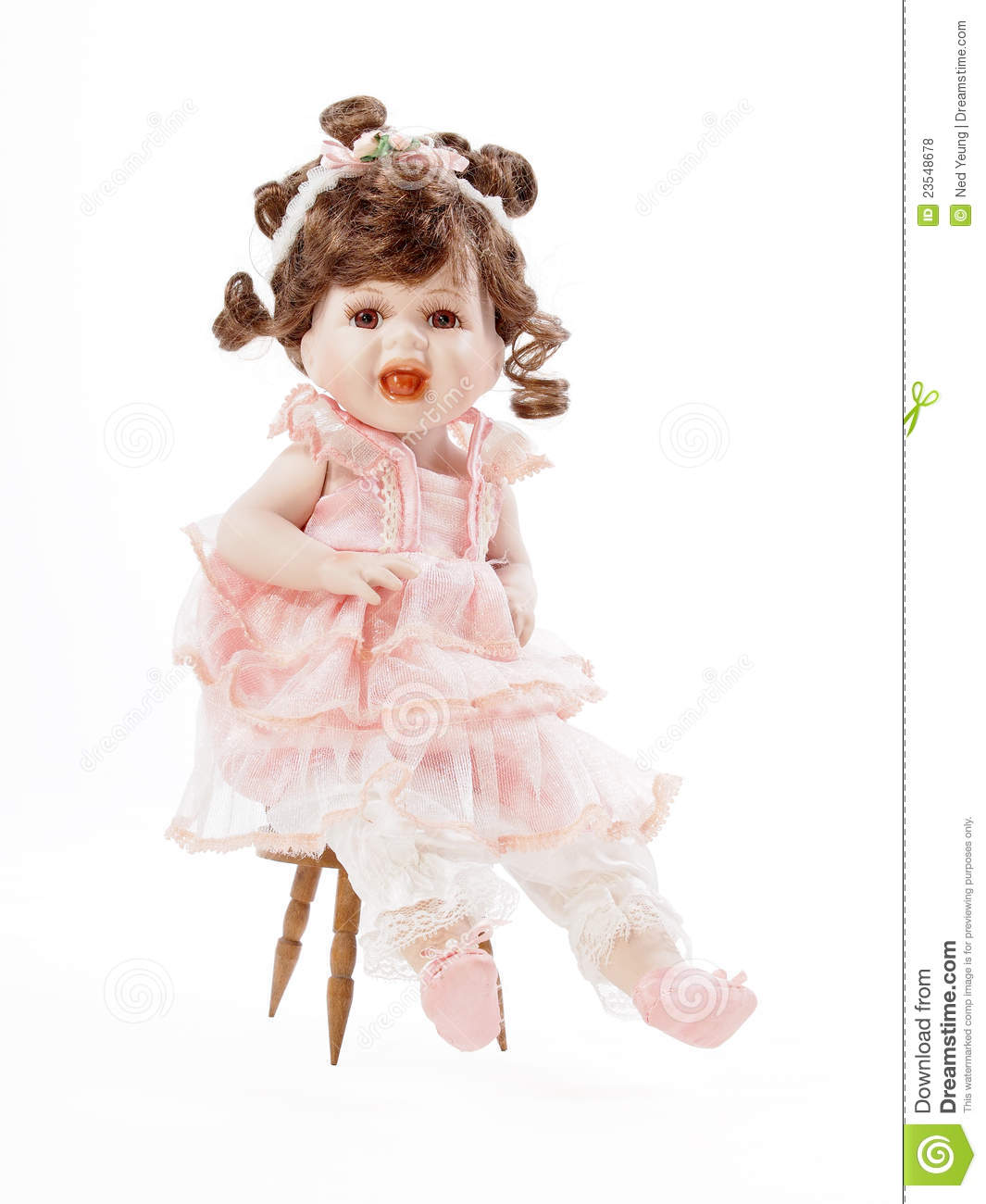 Baby Porcelain Doll Sitting On A Wooden Chair Royalty Free Stock.