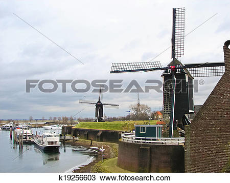 Stock Photo of Ships and windmills in the port city Heusden.