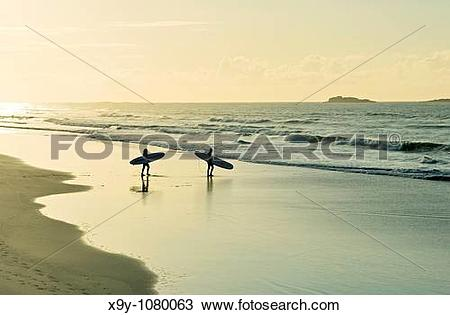 Stock Photo of Surfers carrying surfboards walking along sandy.