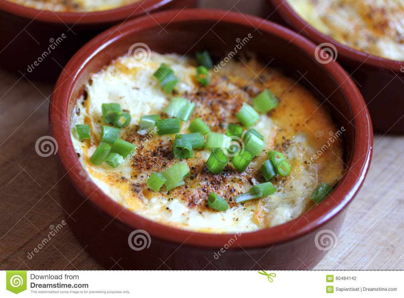 Potato Gratin Baked In A Small Ceramic Dish With A Rustic Setting.