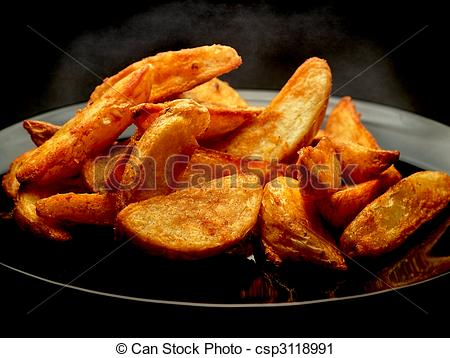 Stock Photography of Hot spicy potato wedges on black plate.