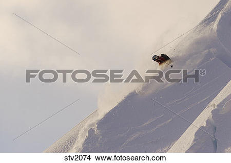 Stock Photo of A woman skiing powder snow in the early morning on.