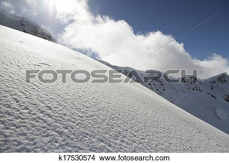 Stock Photo of ski slope in powder snow, mountain landscape.