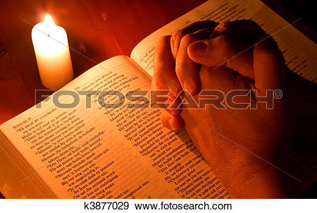 Stock Photograph of Bible by candle light with hands folded in.