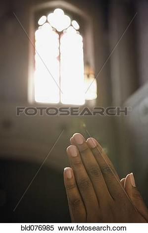Stock Image of Light from church window shining on hands clasped.