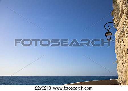 Stock Photography of A lamp mounted to the side of a rock cliff.