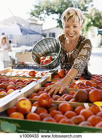 Stock Photo of Mature Woman Picks Nectarines at an Outdoor Market.