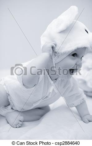 Stock Photography of smiling kid sitting on the bed tries to pull.