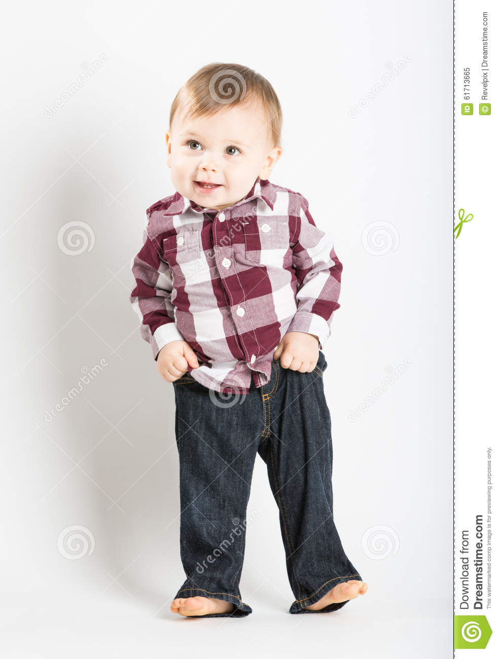 Baby Stands In Flannel And Jeans Pulling Up Pants Stock Photo.