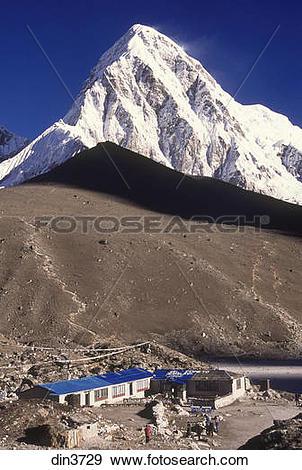 Stock Photograph of Pumori dwarfs the small trekkers lodge at.