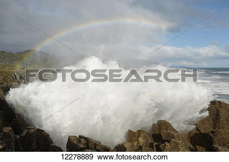 Stock Photograph of Punakaiki blowholes with a rainbow, West Coast.