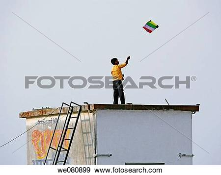Stock Photograph of A boy playing with a kite, kite in flight Pune.