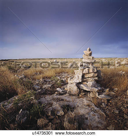 Stock Photography of Small pyramid of rocks in a grass field.