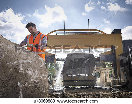 Stock Photo of Quarry worker measuring rock in front of stone saw.