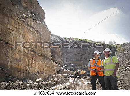 Stock Photo of Quarry workers inspecting rock strata in stone.
