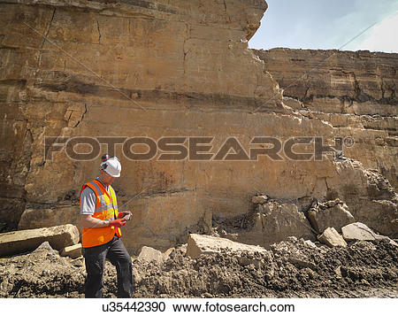 Stock Photography of Quarry worker inspecting stone in quarry.