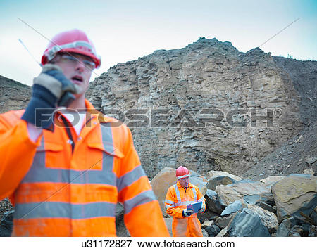 Picture of Quarryman using walkie talkie by cliff face of quarry.