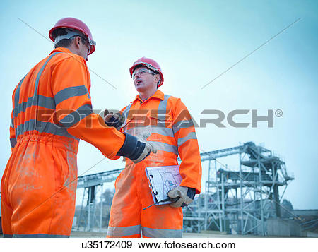 Stock Photograph of Low angle view of quarryman advising.
