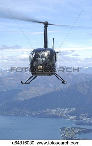 Stock Photography of Robinspon R44 helicopter in flight over Lake.