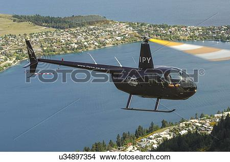Stock Photo of Robinson R44 helicopter in flight over Queenstown.