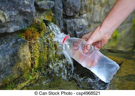 Stock Photography of source of spring water bottle filling holding.