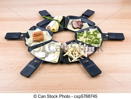 Stock Images of Raclette pans with food, ideal for party.