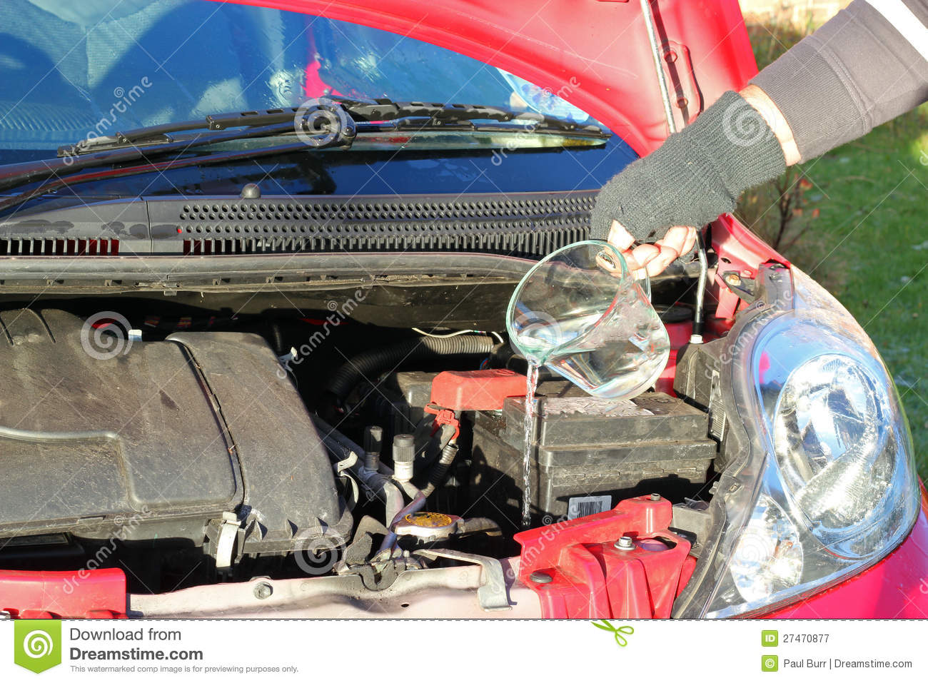 Putting Water Into A Car Radiator. Royalty Free Stock Image.