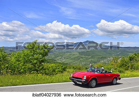 """Stock Images of """"Fiat 124 Spider convertible, classic car, on road."""