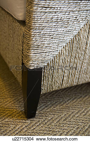 Stock Photo of Leg of wooden and raffia chair on rug u22715304.