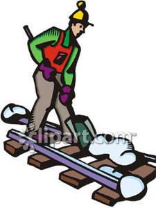 Man Shoveling Snow Off Train Tracks.