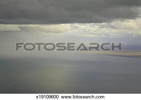 Stock Photography of Cumulus clouds and rain showers over sea.
