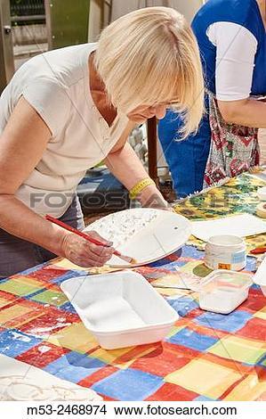 Stock Photo of An amateur artist apply raku glaze on ceramic.