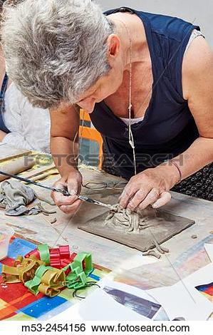 Stock Images of Amateur artists while modeling clay to obtain raku.