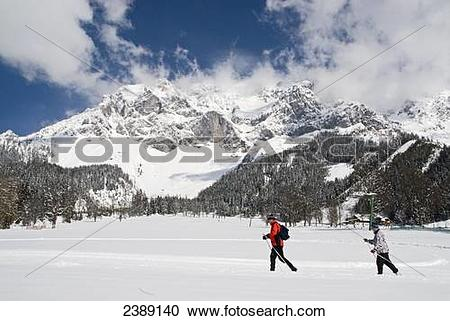 Stock Photography of Tourists skiing on snow covered landscape.
