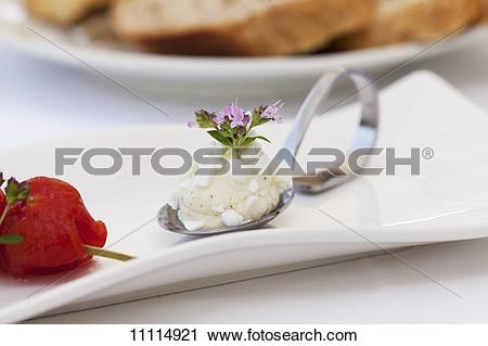 Stock Photography of A spoonful of raw milk goat's cheese and.