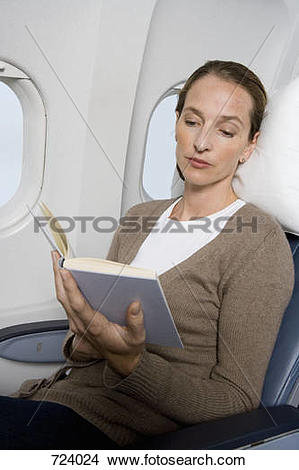 Stock Photo of A female passenger reading on a plane 724024.